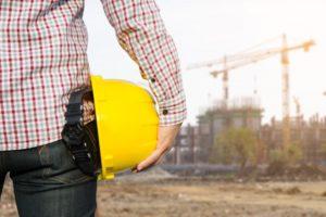 trabajador-del-ingeniero-de-la-mano-que-sostiene-el-casco-de-seguridad-amarillo-con-la-construccion-en-fondo-del-sitio_1439-9